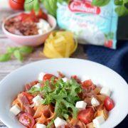Tagliatelle w pomidorowym sosie z prosciutto, pomidorkami i mozzarellą